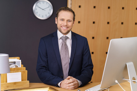 Confident young hotel manager with a welcoming smile standing waiting to greet visitors at the front desk of a luxury hotel