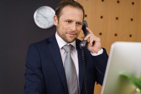 Apuesto joven director del hotel comprobar la información sobre su computadora de escritorio en la recepción frente mientras se escucha una llamada de un cliente Foto de archivo