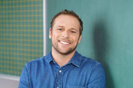 Jonge man in zijn jaren '30 glimlachen naar de camera staande in blauw shirt naast groene schoolbord