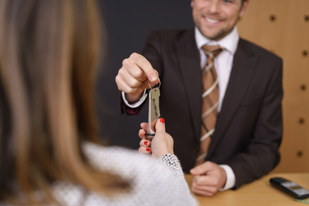 Smiling hotel manager handing over a door key to a woman customer after checking her in to the hotel, selective focus to his hand and the key