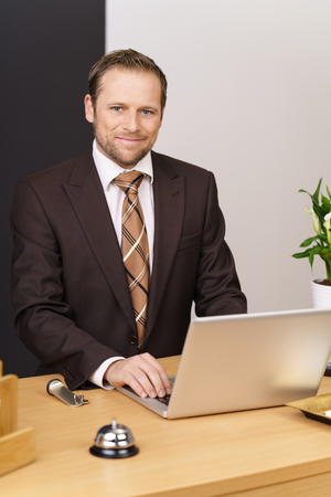 Concierge wearing brown suit smiles at camera as he holds a hand to his computer