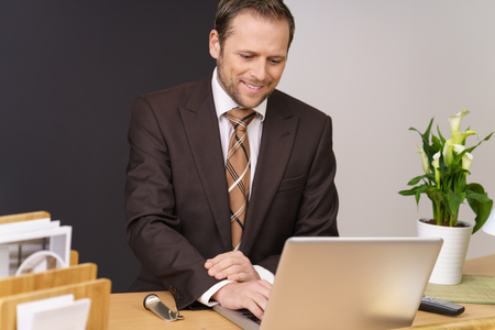 One business man wearing brown suit smiles in his office as he sits before the computer