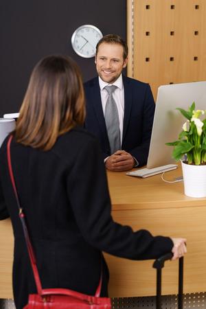 一个时尚的女人拿着她的手提箱在前台一个友好微笑的经理的帮助下预订进一个高档酒店