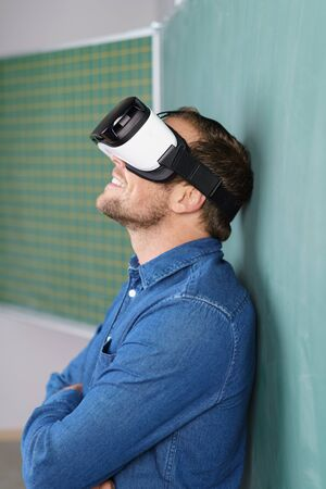 visualizing: Side view of young man in blue shirt wearing 3D glasses throwing head back standing with arms folded leaning back on chalkboard Stock Photo