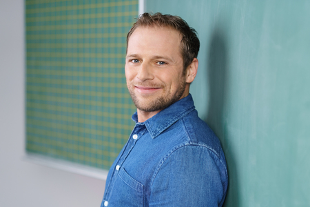 Young man in his 30s wearing blue shirt standing in classroom leaning back on green chalkboard