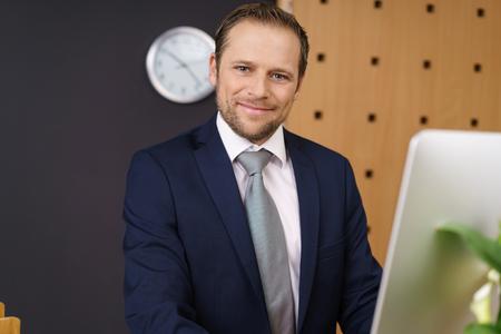 Freundliches Hotel-Manager mit einem warmen, einladenden Lächeln hinter seinem Computer von einem Luxushotel an der Rezeption stehen Standard-Bild - 71908371