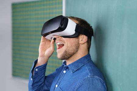 Close up of young man wearing VR headset 3D glasses delightfully looking up with his mouth open, standing next to chalkboard