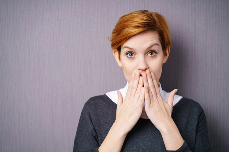 reacts: Shocked young woman with wide eyes and her hands to her mouth as she reacts to something , head and shoulders on grey Stock Photo