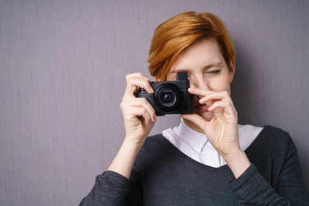 focuses: Young woman taking a photo with a compact camera holding it to her eye as she composes and focuses the shot