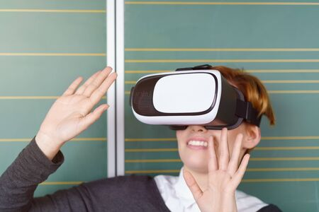 reacting: Young woman reacting to her VR environment raising her hands with a smile as she wears a virtual reality headset