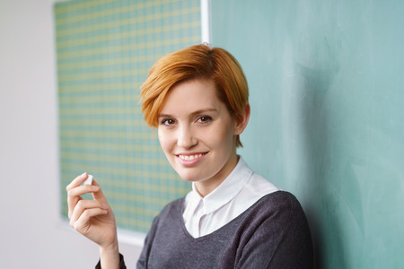 Pretty young woman with short haircut standing near green chalkboard in classroom with piece of chalk, smiling and looking at camera
