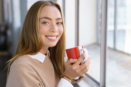 cradling: Vivacious happy young woman drinking coffee as she stands in front of a window cradling a mug in her hands grinning at the camera