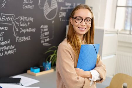 economic: Happy blonde woman in beige sweater and glasses standing in office next to chalkboard, holding blue folder, looking at camera and smiling. Copy space