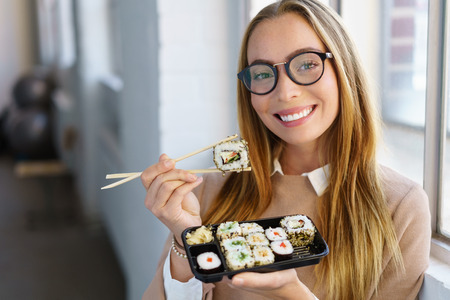Friendly young woman wearing glasses enjoying a fresh sushi takeaway for lunch in the office smiling as she anticipates her next mouthful