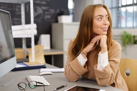 Young businesswoman turning in her chair at her desk in the office to watch off frame to the right with a smile