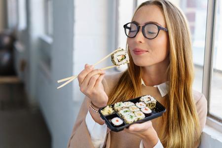 Mujer joven saboreando su sushi almuerzo de pie delante de una ventana en la oficina con los ojos cerrados y una expresión de felicidad mientras se anticipa a la siguiente bocado Foto de archivo - 72768468