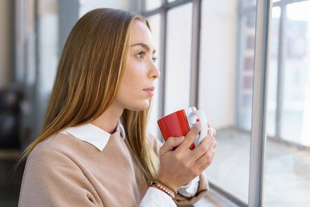 cradling: Young woman daydreaming looking out of a window cradling a coffee mug in her hands with a faraway pensive expression