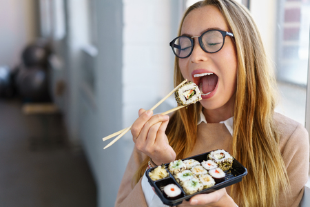 Hungry young woman eating takeaway sushi opening her mouth wide for the next mouthful on her chopsticks with her eyes closed in pleasure and anticipation Standard-Bild