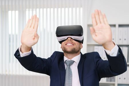 interactivity: Young man in suit experiencing virtual reality in VR headset with his hands up as if groping invisible wall standing in white office interior