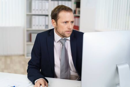 businessman suit: Front portrait of young businessman in suit sitting at office desk and looking at computer screen