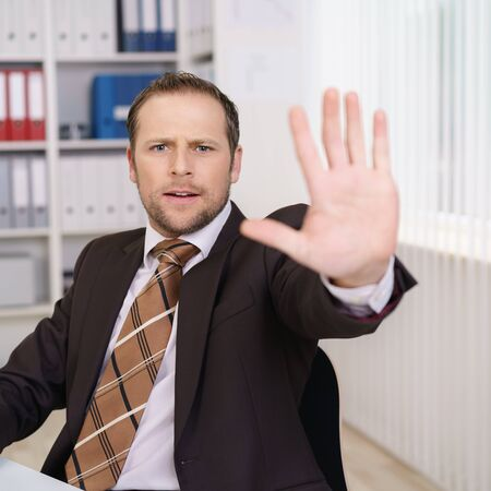 Businessman calling a halt with his hand in the air and a concerned serious expression as he sits at a desk in the office
