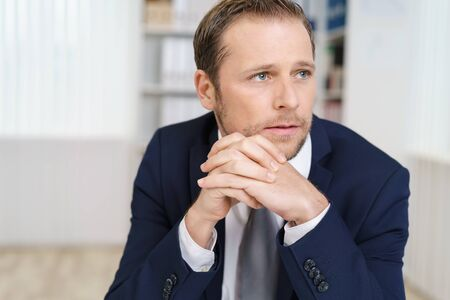 emotionless: Emotionless young handsome businessman in suit looking away sitting with fingers locked at office desk, close-up portrait Stock Photo