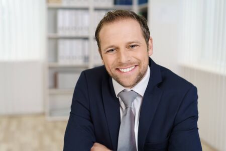 Smiling handsome young businessman close-up portrait sitting in office with blurred background