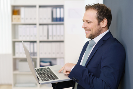 trackpad: Young businessman in suit standing and holding laptop in his hand, looking on screen and smiling, moving his finger over trackpad. Side portrait in office interior