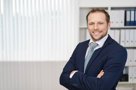 Young businessman in dark blue suit standing with his arms crossed, looking at camera and smiling. Office interior blurred in background with white blinds as copy space Stock Photo