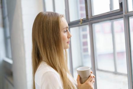 しんみりと窓の外を見つめて両手でマグカップとコーヒー ブレークの地位を取って思いやりのある若い女性 写真素材