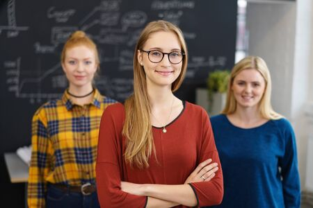 Smiling confident leader with her business team standing in the foreground with folded arms beaming at the camera