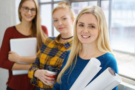 Three young female students on campus standing in front of a window with paperwork and rolled drawings or plans with focus to a smiling blond woman in front Stock Photo