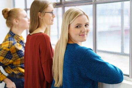 Three young women students relaxing between classes standing together looking out of a window with one attractive blond girl turning to smile at the camera