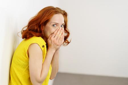 Une jeune rouquine coupable ou embarrassée couvre sa face inférieure avec ses mains et jette un coup d'?il de côté à la caméra avec de grands yeux alors qu'elle s'appuie contre un mur Banque d'images - 74155609