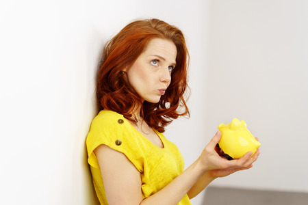 Young woman holding a piggy bank with a pensive expression grimacing as she tries to decide if she should spend her nest egg or continue saving