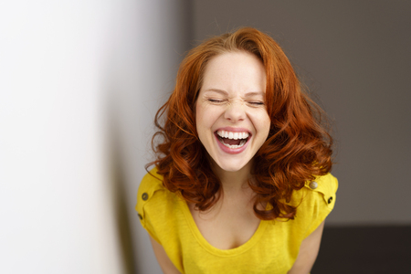 Pretty young woman enjoying a good joke having a hearty laugh with mouth open and eyes closed as she leans towards the camera Stock Photo