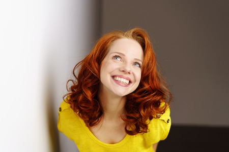 Cute flirtatious pretty young redhead woman leaning forwards towards the camera with a cheeky grin