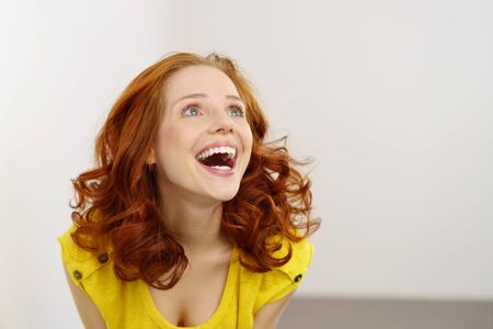 happy woman: Beautiful red haired woman laughing or happy and surprised when looking up, standing in yellow shirt against white wall in background with copy space