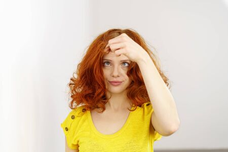 Tousled redhead squinting at a lock of her hair that she is holding in front of her face with her fingers