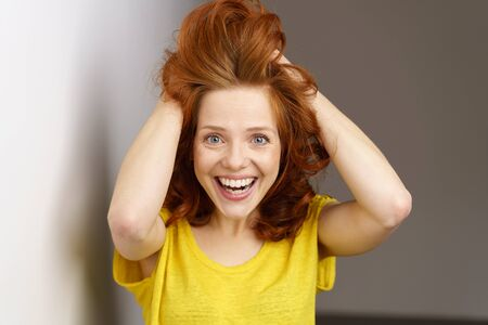 Excited overjoyed attractive young woman running her hands through her coppery red hair with a look of wonderment and beaming smile of pleasure Stock Photo
