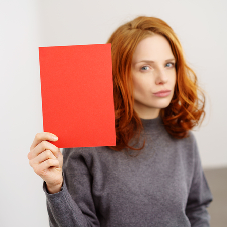 Speculative young redhead woman holding up a blank red card with copy space in her hand with focus to the sign