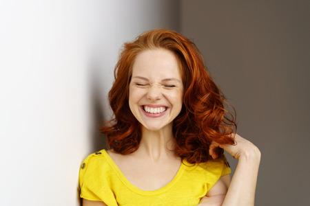 Aufgeregte junge Frau, die ein doofes Gesicht mit einem breiten Lächeln ziehen, als sie mit ihrem schulterlang roten Haaren spielt