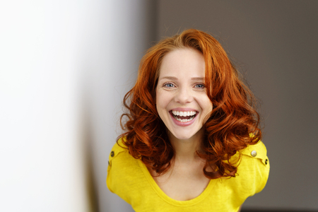 exuberant: Exuberant extrovert young redhead woman laughing at the camera with a beaming vivacious smile as she leans forwards Stock Photo