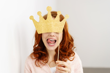 Playful young redhead woman holding a golden crown party or photo booth accessory covering her eyes as she stick out her tongue playfully at the camera