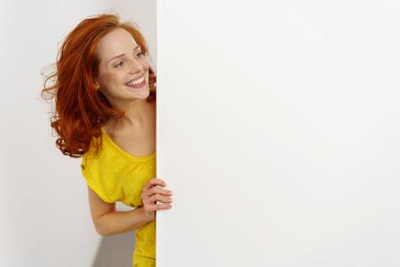 Gelukkige vriendschappelijke jonge vrouw met een leeg wit uithangbord met exemplaarruimte die rond de kant met een brutale grijns tuurt