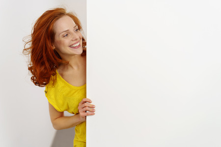 Glückliche freundliche junge Frau mit einem leeren weißen Schild mit dem Kopienraum, der um die Seite mit einem unverschämten Grinsen peering ist