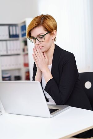 concentrates: Thoughtful businesswoman reading her laptop screen with her hands clasped in front of her face as she concentrates on the information