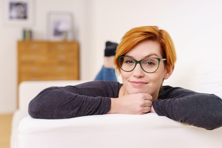 woman lying: Quizzical disbelieving attractive young redhead woman wearing glasses raising an eyebrow to show her scepticism Stock Photo