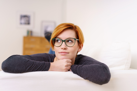 Thoughtful woman with a pensive expression relaxing on a couch with her chin on her hands looking sideways up into the air in a close up view