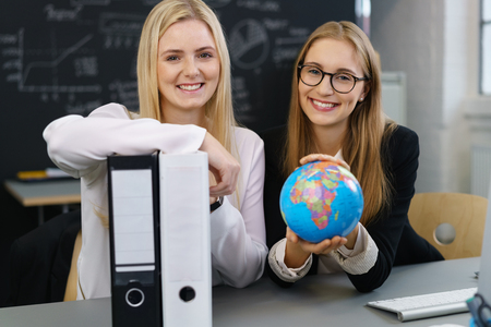 Pair of cute women holding globe and binders as they are seated at a desk in school classroom setting